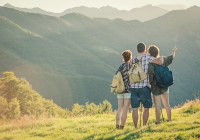 Three friends stand looking at view of mountains