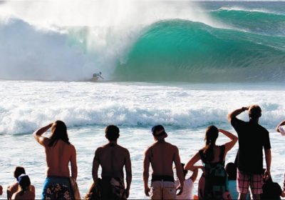 surfer riding wave in front of a crowd
