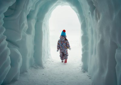 little girl comes out of an ice cave in a winter park